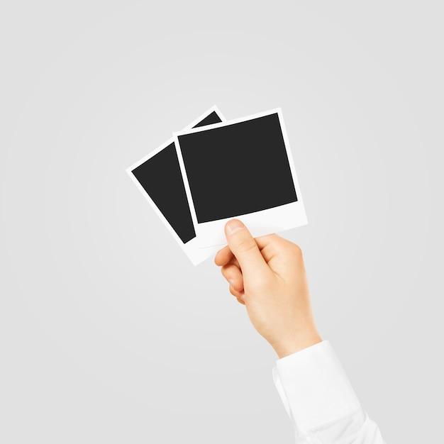 Mão segurando molduras em branco Foto Premium
