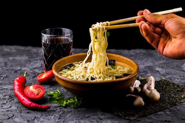 Mão, segurando, noodles, com, chopsticks Foto gratuita