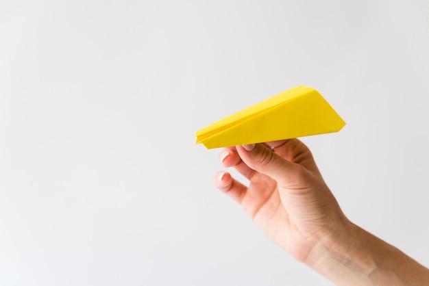 Mão segurando o avião de papel amarelo Foto gratuita