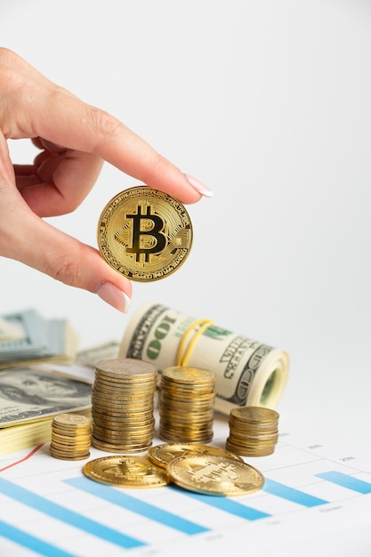 Mão segurando o bitcoin acima da pilha de moedas Foto gratuita