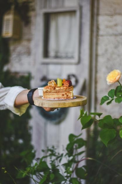 Mão segurando o bolo russo medovik mel no topo morango ang kiwi Foto Premium