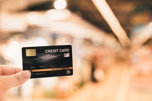 Mão segurando o cartão de crédito com o conceito de supermercado, compras e varejo de borrão Foto Premium