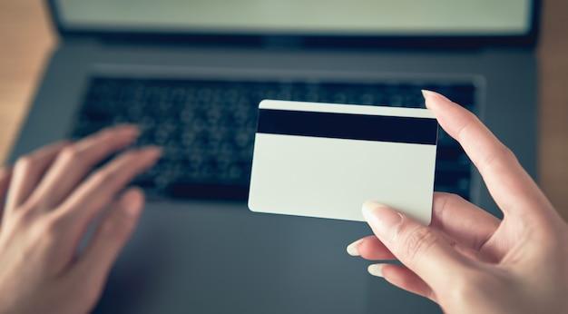 Mão segurando o cartão de crédito e pressione o computador portátil digite o código de pagamento para o produto. Foto Premium