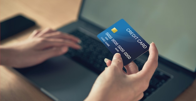 Mão segurando o cartão de crédito e pressione o laptop, digite o código de pagamento do produto Foto Premium