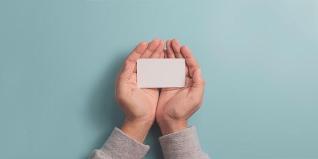 Mão segurando o cartão de nome da empresa em branco sobre fundo azul, com espaço de cópia para o texto de entrada e o ícone do infográfico. Foto Premium