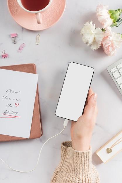 Mão segurando o celular em branco Foto gratuita