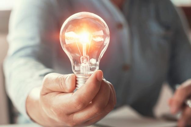 Mão segurando o conceito de energia de lâmpada Foto Premium