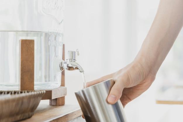 Mão segurando o copo de aço inoxidável enquanto enche a água potável. Foto Premium