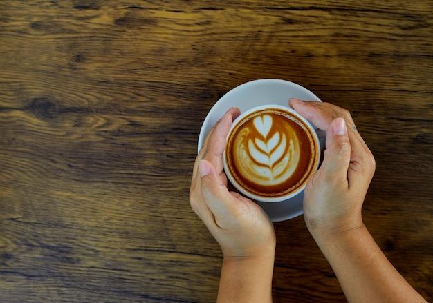 Mão segurando o copo de café na mesa Foto Premium