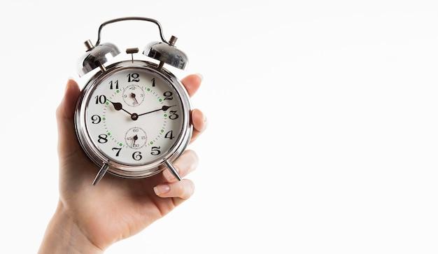 Mão segurando o despertador com espaço de cópia Foto gratuita