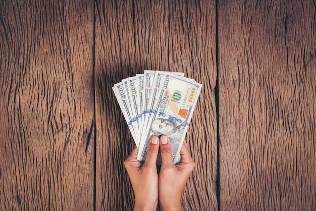 Mão segurando o dinheiro de notas de dólar em fundo de madeira Foto gratuita
