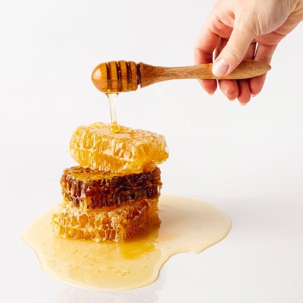 Mão segurando o dipper sobre a torre de favos de mel Foto gratuita