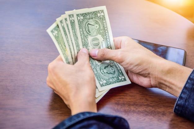 Mão segurando o dólar para fazer compras, economia de notas de dinheiro e conceito de investimento Foto Premium