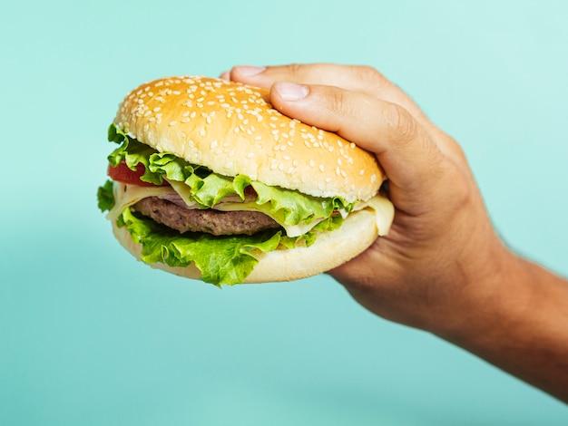 Mão segurando o hamburguer delicioso com fundo azul Foto gratuita