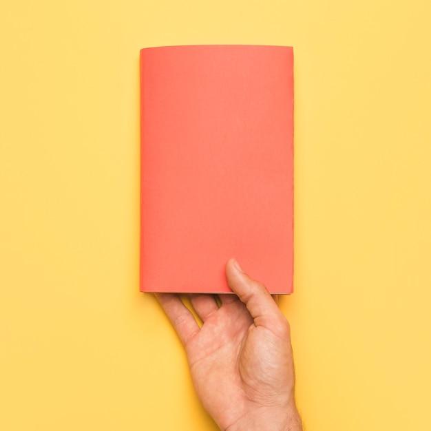 Mão segurando o livro com capa vermelha Foto gratuita