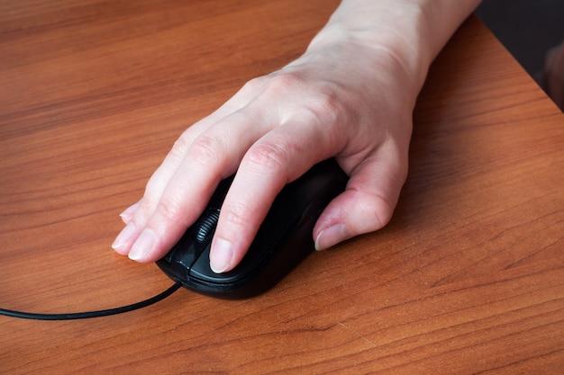 Mão segurando o mouse do computador. fechar-se. mesa de madeira. Foto Premium