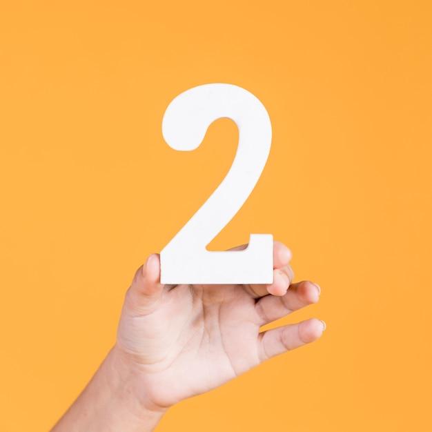 Mão segurando o número dois sobre fundo amarelo Foto gratuita