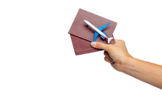 Mão segurando o passaporte isolado no branco Foto Premium