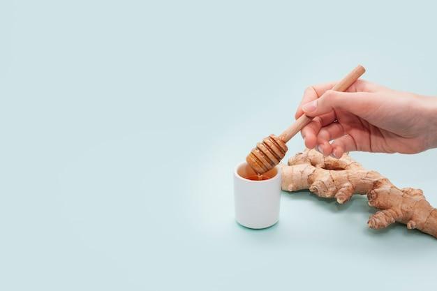 Mão segurando o pau de mel com espaço de cópia Foto gratuita