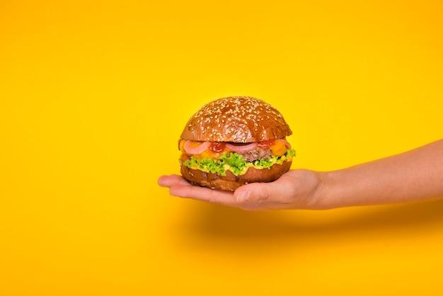 Mão segurando o saboroso hambúrguer de carne Foto gratuita