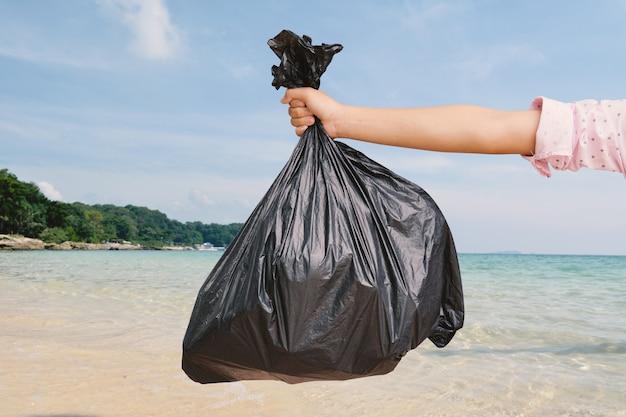 Mão segurando o saco plástico bin na beira-mar Foto Premium