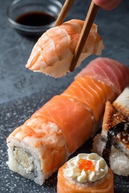 Mão segurando o sushi de pauzinhos com camarão no fundo da mesa cinza Foto Premium