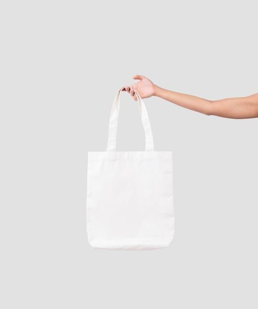 Mão segurando o tecido de lona de saco para modelo em branco de maquete isolado em fundo cinza. Foto Premium