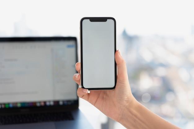 Mão segurando o telefone na frente do modelo de computador portátil Foto gratuita