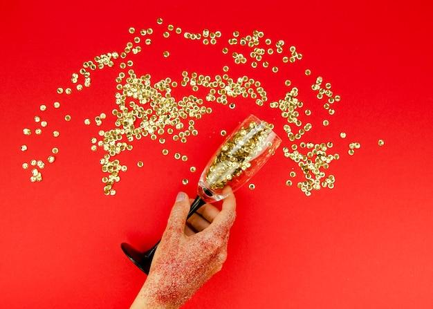 Mão segurando o vidro com glitter dourado Foto gratuita