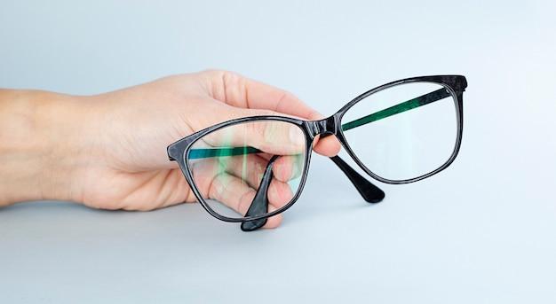 Mão segurando óculos escuros Foto Premium