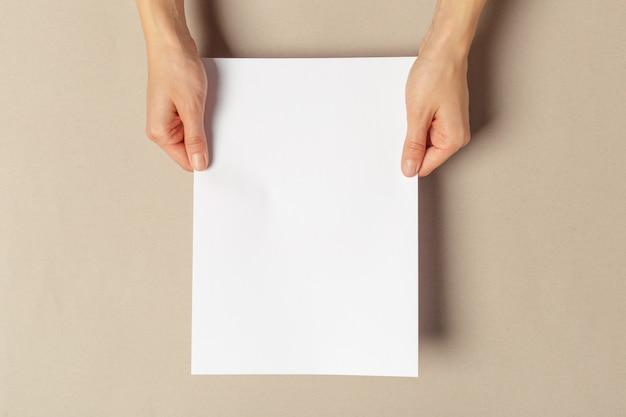 Mão segurando papéis tamanho a4 Foto Premium