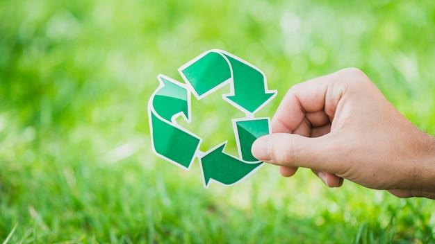 Mão, segurando, recicle símbolo, contra, grama verde Foto gratuita