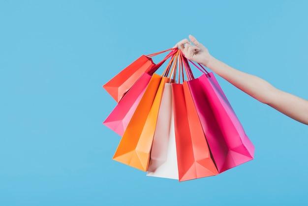 Mão segurando sacolas de compras no fundo liso Foto Premium