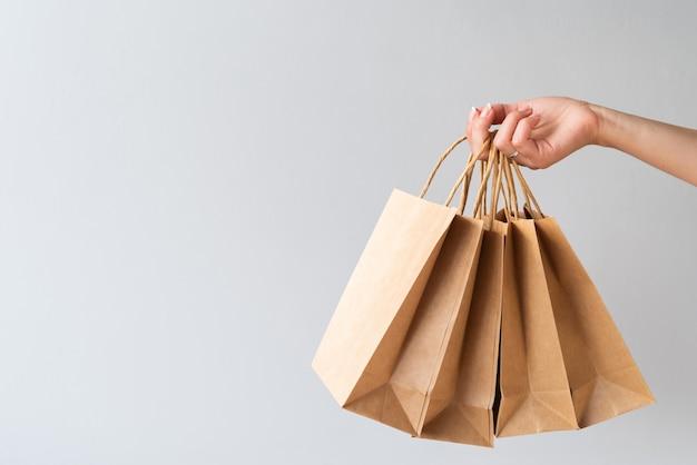 Mão segurando sacos de papel com cópia-espaço Foto gratuita