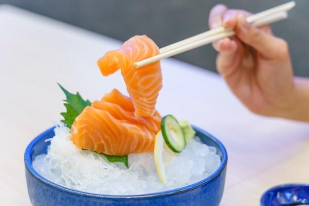 Mão, segurando, salmão, sashimi, usando, chopsticks - fresco, salmão fresco, cortado Foto Premium