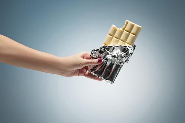 Mão segurando um azulejo de chocolate branco Foto gratuita