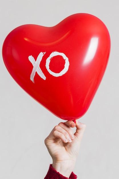 Mão segurando um balão de coração Foto gratuita