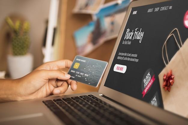 Mão segurando um cartão ao lado de um laptop simulado Foto gratuita