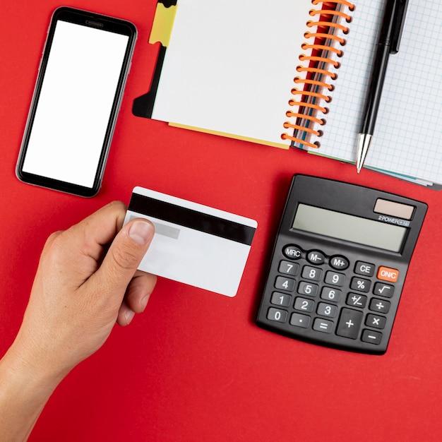Mão segurando um cartão de crédito ao lado de um telefone simulado Foto gratuita
