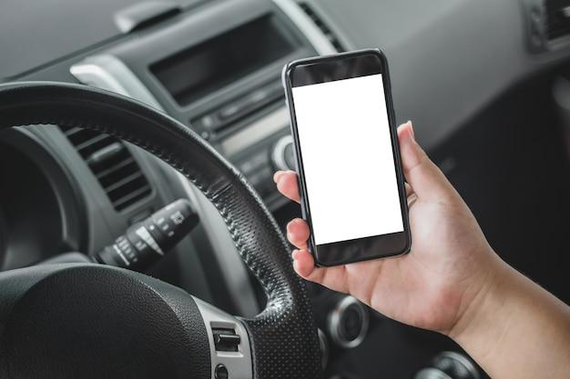 Mão segurando um celular em um carro Foto gratuita