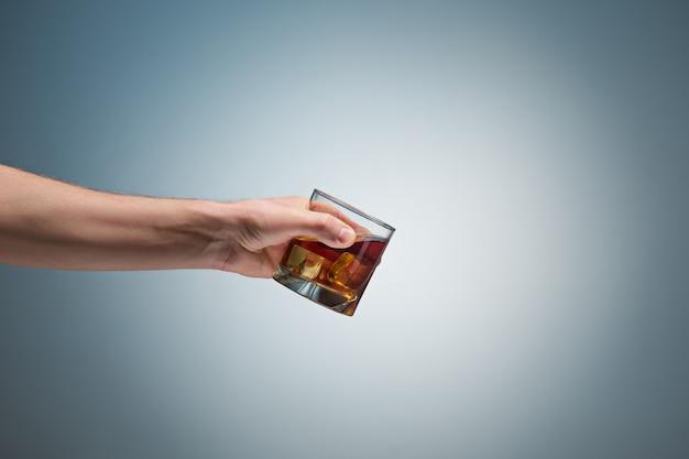 Mão segurando um copo de uísque Foto gratuita