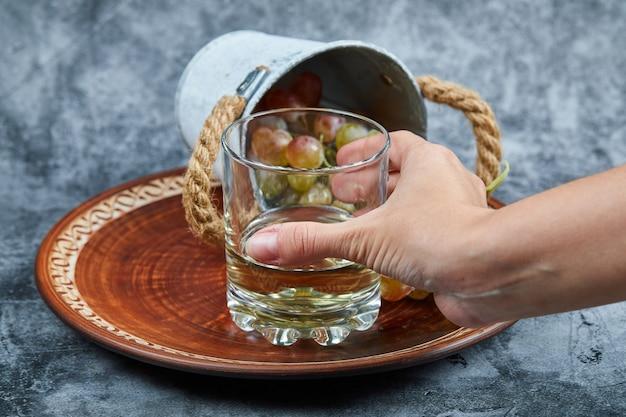 Mão segurando um copo de vinho branco e um pequeno balde de uvas em uma superfície de mármore. Foto gratuita