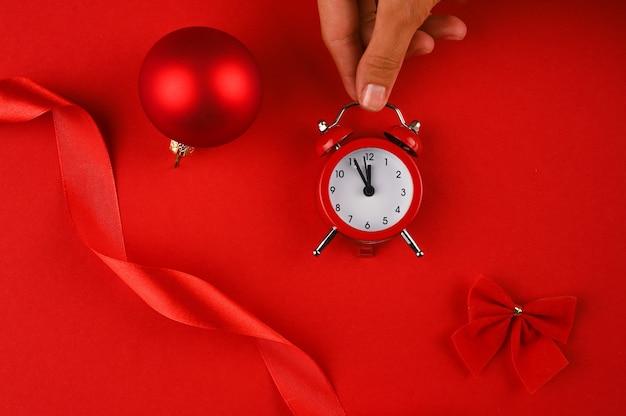 Mão segurando um despertador vermelho sobre fundo vermelho com elementos de natal. Foto Premium
