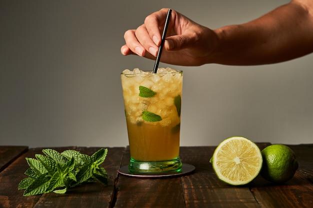 Mão segurando um mojito pronto para beber no bar Foto Premium