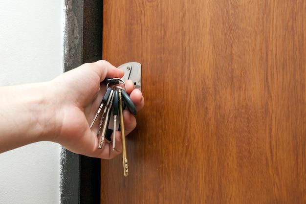 Mão segurando um molho de chaves diferentes no buraco da fechadura Foto Premium