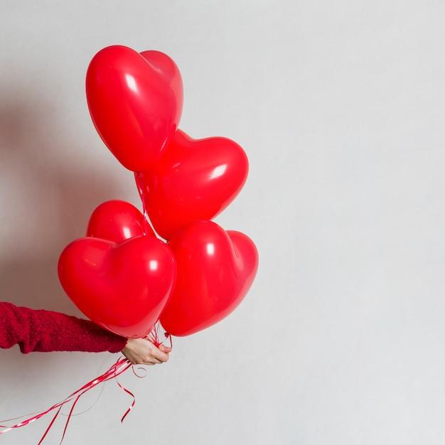 Mão segurando um monte de balões Foto gratuita