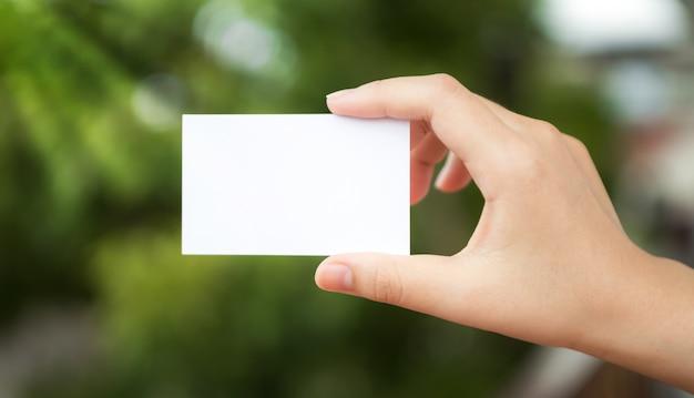 Mão segurando um papel branco com o fundo desfocado Foto gratuita
