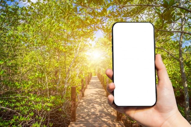 Mão segurando um smartphone em branco sobre fundo de paisagem natural Foto Premium