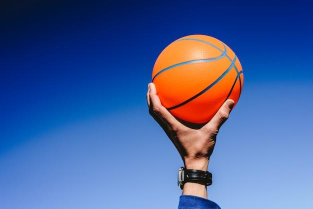 Mão segurando uma bola de basquete laranja no fundo do céu azul Foto Premium