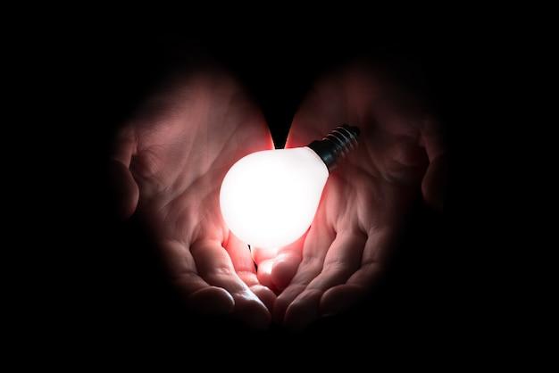 Mão segurando uma lâmpada incandescente Foto Premium